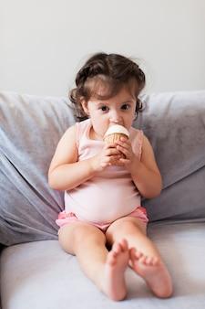 Linda chica comiendo helado en el sofá