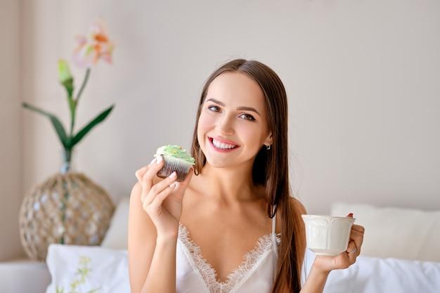 Linda chica comiendo pastel y bebiendo té en la cama
