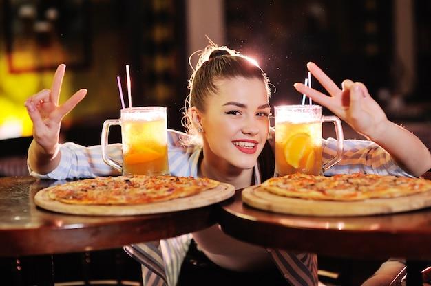 Linda chica comiendo pizza y bebiendo cerveza o un cóctel de cerveza cítrica de un bar o pizzería.