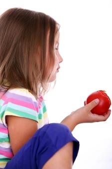 Linda chica comiendo un tomate