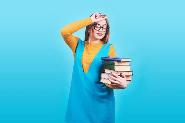 Linda chica confundida sosteniendo en las manos una pila de libros aislados en azul colorido