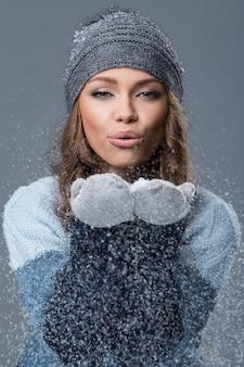 Linda chica con copos de nieve pasando un buen rato