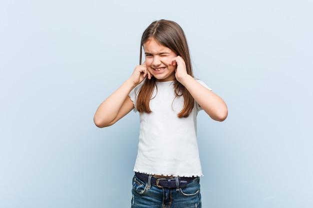 Linda chica cubriendo las orejas con las manos.