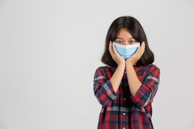 Linda chica está cubriendo su rostro mientras usa la máscara en la pared blanca.