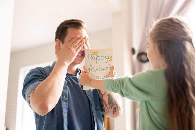 Linda chica dando tarjeta navideña al padre mientras él cubre los ojos con las manos en previsión del regalo de la hija