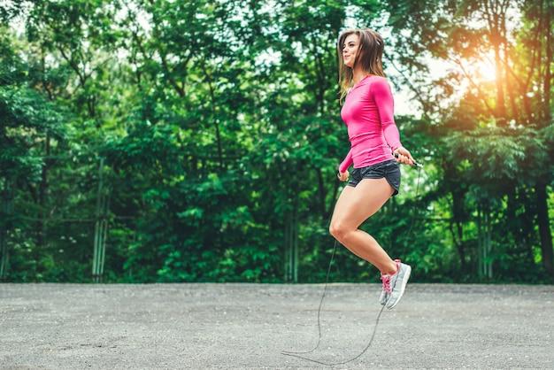 Linda chica deportiva con entrenamiento de cuerda al aire libre