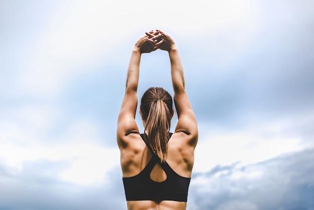 Linda chica deportiva mostrando ejercicios de estiramiento al aire libre