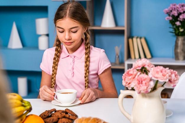 Linda chica desayunando por la mañana en casa