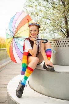 Linda chica desexual con lgbt rainbow en su rostro con botas masculinas en calcetines coloridos y posando con paraguas al aire libre