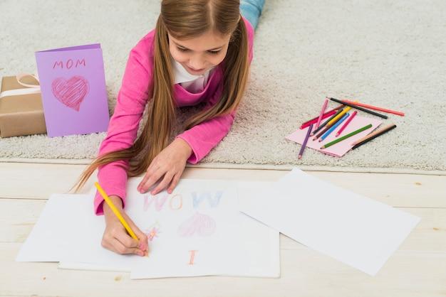 Linda chica dibujo amo a mamá sobre papel