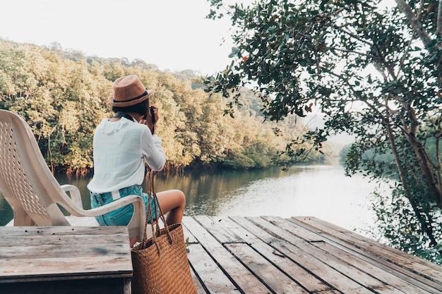 Linda chica disfruta con la naturaleza descansando y mirando en el río.