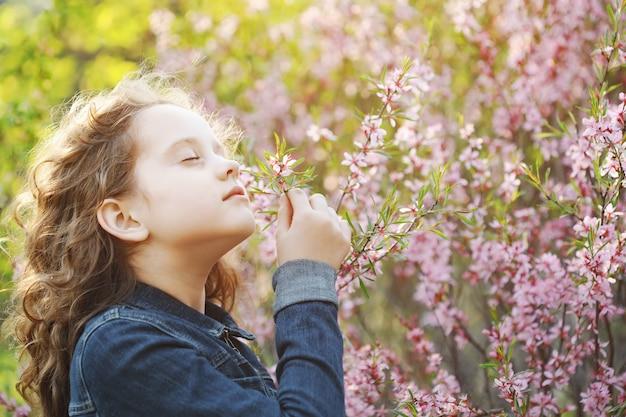 Linda chica disfruta del olor de la flor de la almendra en flor. concepto saludable, médico.