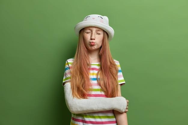 Una linda chica divertida hace muecas y hace pucheros en los labios, tiene la cara pecosa y el pelo largo y astuto, posa con yeso en el brazo roto, se lesionó durante las vacaciones de verano, usa una camiseta a rayas y un sombrero.