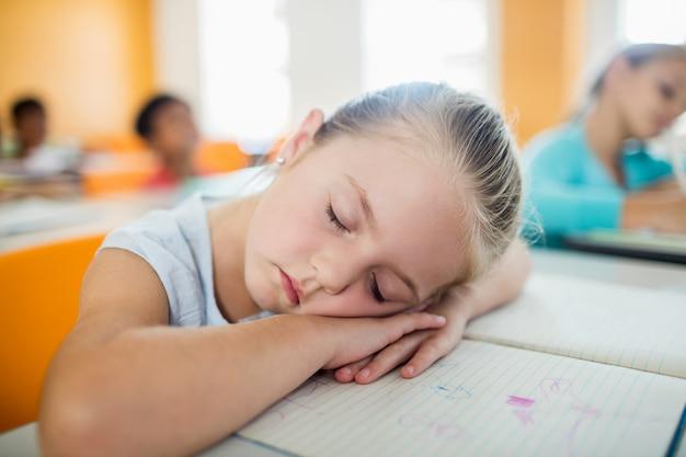 Una linda chica durmiendo en el escritorio
