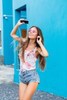 Linda chica elegante sobre fondo azul baila y escucha música con auriculares en el teléfono inteligente.