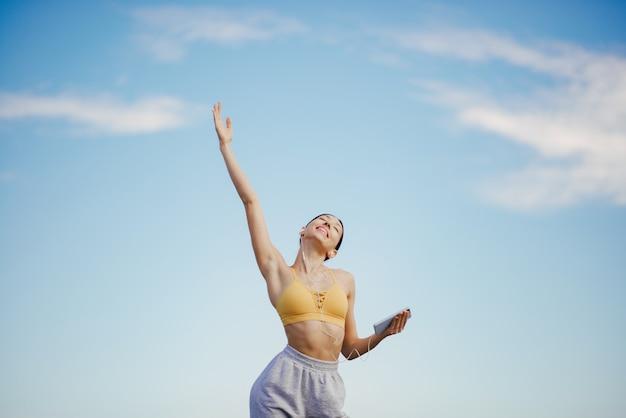 Linda chica con entrenamiento telefónico en cielo azul