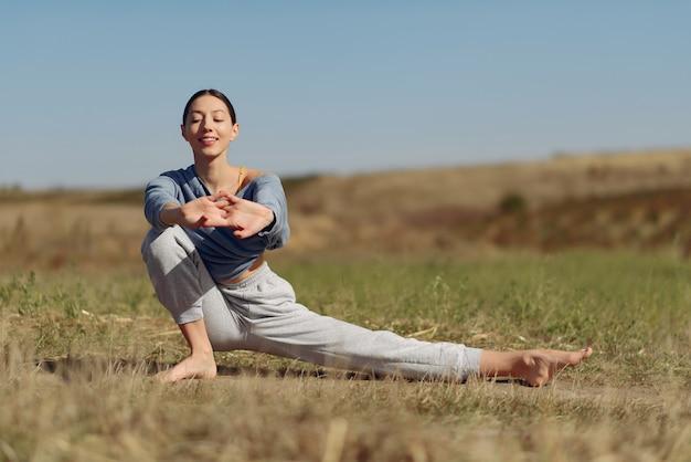 Linda chica entrenando en el cielo azul en un campo