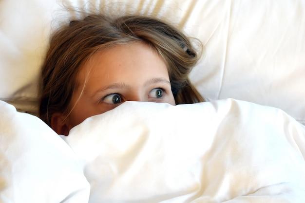 Linda chica escondida debajo de las sábanas