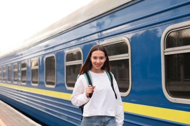 Linda chica en la estación de tren sonríe