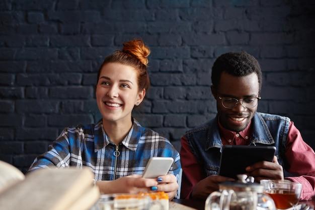 Linda chica estudiante con mensajes de cabello pelirrojo a través de las redes sociales, su guapo compañero africano sentado a su lado con tableta digital, ambos con apariencia alegre
