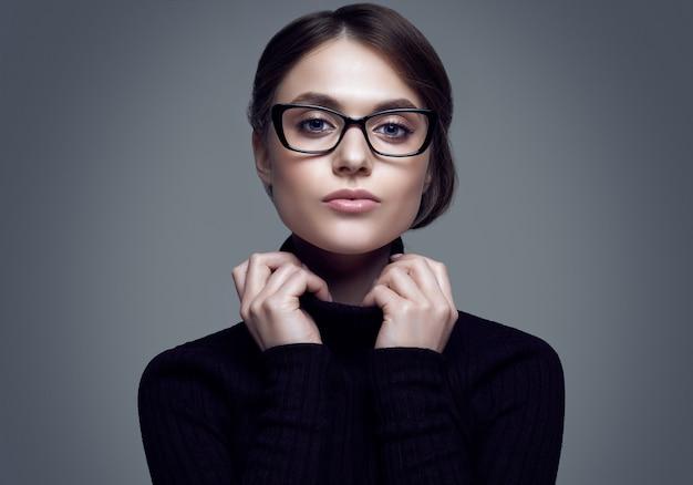 Linda chica estudiante con suéter de cuello alto negro y lentes con estilo