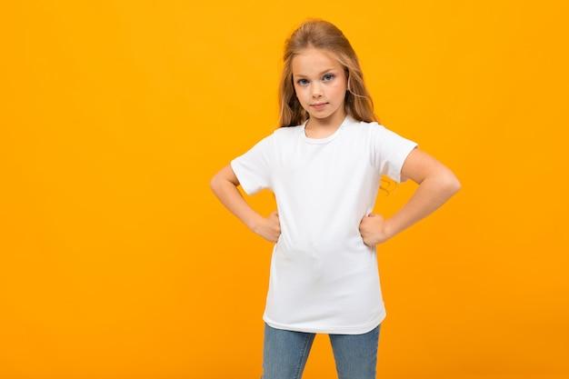 Linda chica europea en una camiseta blanca con una maqueta en una pared amarilla