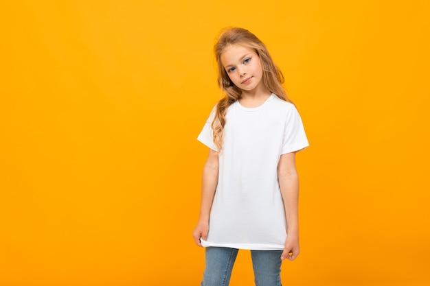 Linda chica europea en una camiseta blanca sobre una pared amarilla