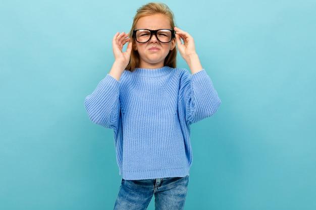 Linda chica europea entrecerrando los ojos en gafas de color azul claro