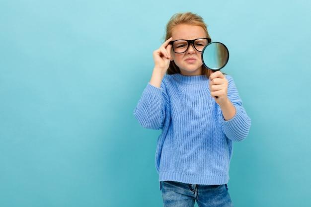 Linda chica europea en gafas mira a través de una lupa en azul claro