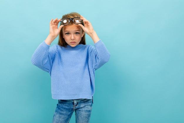Linda chica europea se quitó las gafas con la cabeza en azul claro