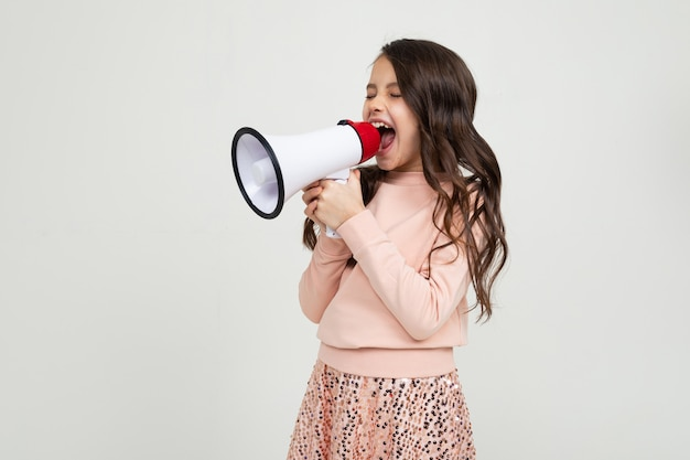 Linda chica europea sonriente con un megáfono informa las noticias con un megáfono en manos sobre una pared blanca del estudio