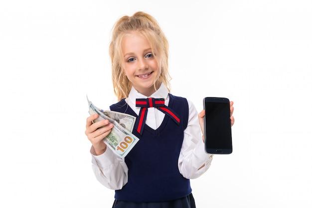 Linda chica europea tiene dinero y un teléfono con una maqueta en blanco