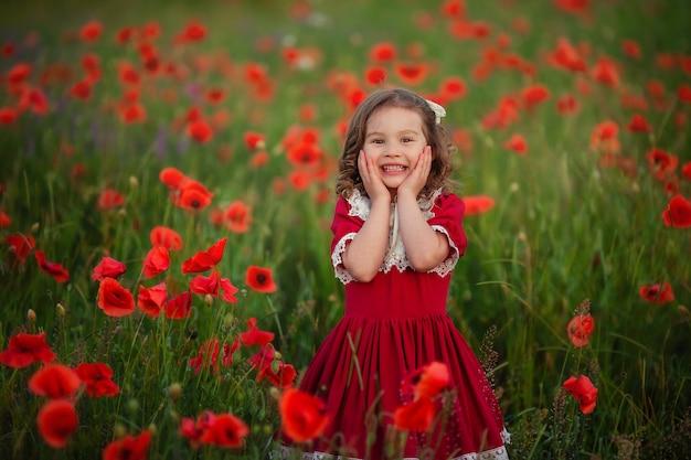 Linda chica feliz con el pelo rizado en un vestido rojo vintage con encaje en los rayos del sol poniente en un campo de amapolas.
