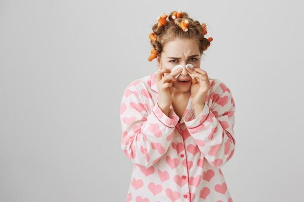 Linda chica feliz en ropa de dormir y rizadores de pelo limpie el maquillaje con almohadillas de algodón