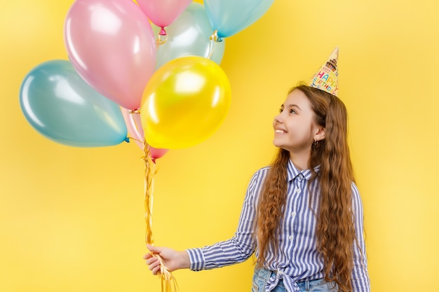 Linda chica en fiesta de cumpleaños con coloridos globos inflables aislado en una pared amarilla