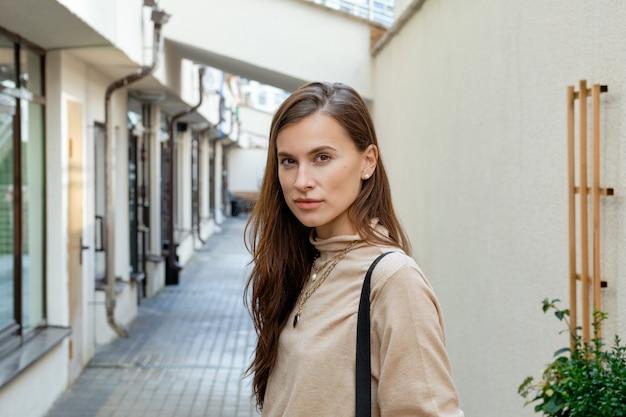 Linda chica frente a la entrada de apartamentos