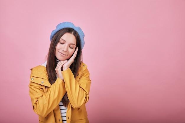 Linda chica fresca en chaqueta de lluvia amarilla con ojos cerrados y sonrisa