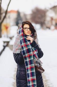 Linda chica en gafas y una bufanda