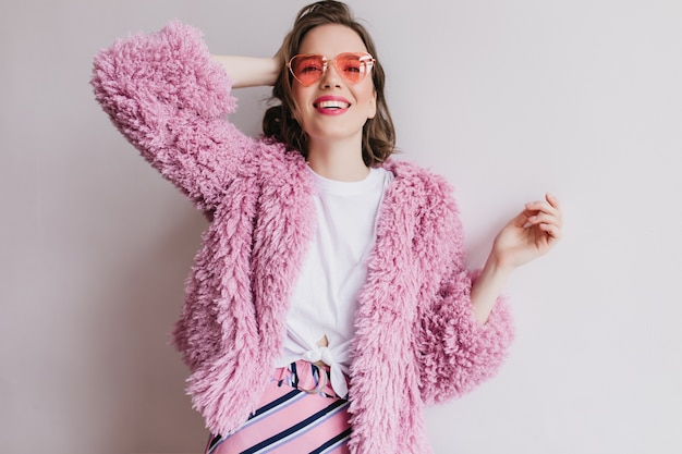 Linda chica en gafas de sol rosa posando con sonrisa alegre en la pared blanca. retrato de interior de mujer de pelo corto en abrigo de piel jugando con su cabello.