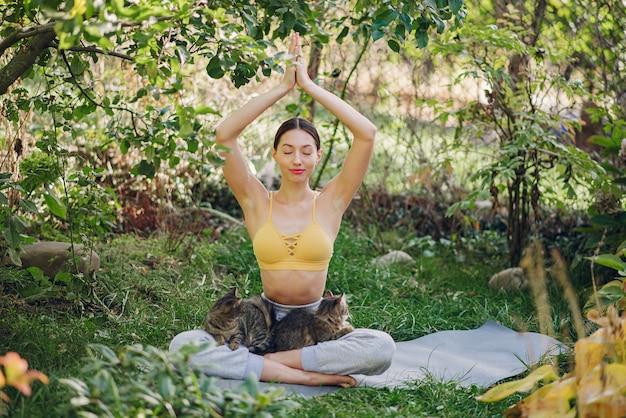 Linda chica con un gato entrenando en un patio de verano