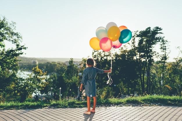Linda chica con globos de colores en el parque de la ciudad soñando