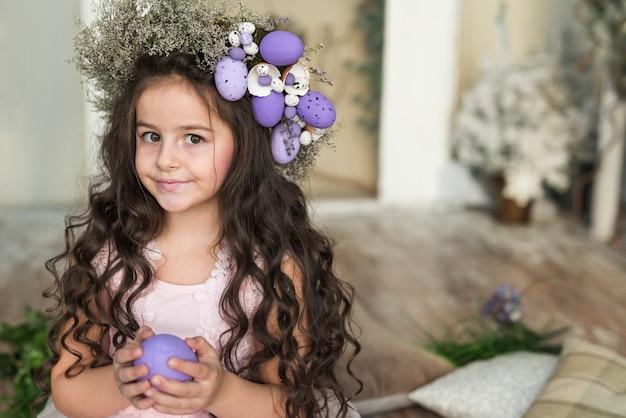 Linda chica en guirnalda de flores con huevo de pascua