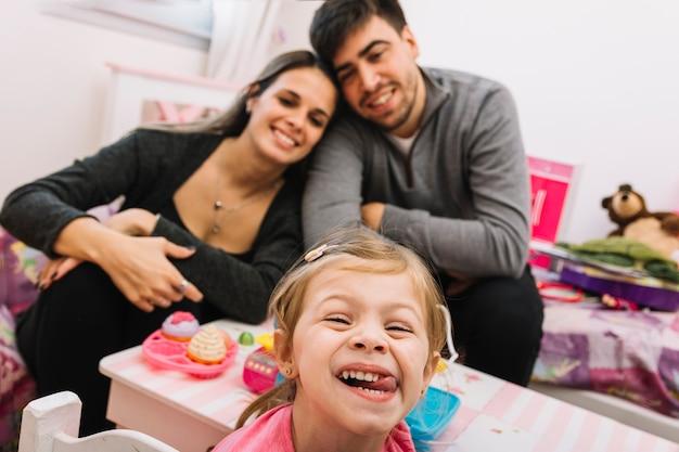 Linda chica haciendo cara graciosa delante de sus felices padres