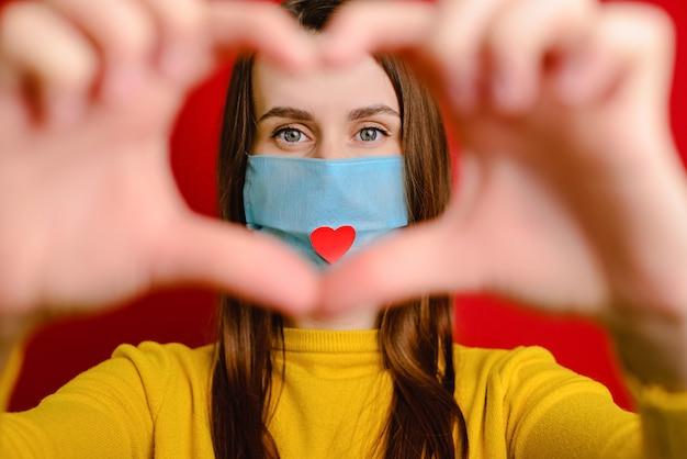 Linda chica haciendo un gesto con la mano en forma de corazón mirando a la cámara, usa una máscara médica con un corazón rojo como una forma de mostrar agradecimiento y agradecer a todos los empleados esenciales durante la pandemia covid-19