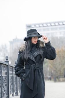 Una linda chica con un hermoso abrigo gris y un sombrero camina en el parque en un frío otoño