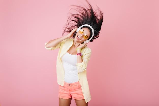 Linda chica hispana con piel bronceada con brazalete de moda y gafas naranjas escuchando música y bailando. foto interior de atractiva dama latina en chaqueta de algodón amarillo divirtiéndose.