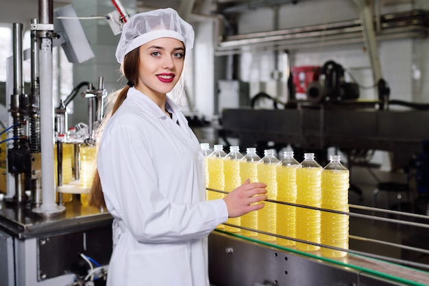 Linda chica joven con una botella de girasol o aceite de oliva