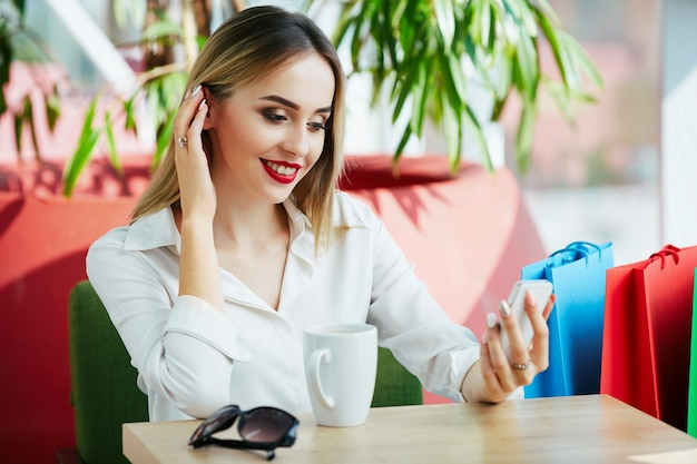 Linda chica joven con cabello castaño claro y labios rojos con blusa blanca y sentada con coloridas bolsas de la compra y taza de café, sosteniendo el teléfono móvil, concepto de compras.