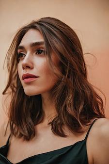 Linda chica joven con cabello ondulado morena, ojos oscuros y maquillaje elegante posando en vestido de correa contra la pared de la pared de melocotón y mirando a otro lado