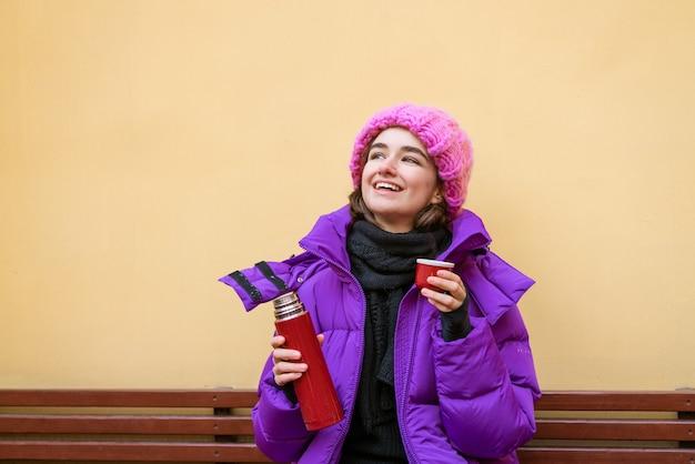 Linda chica joven con cabello oscuro en chaqueta rosa se sienta en un banco de madera y bebe té caliente de la ...